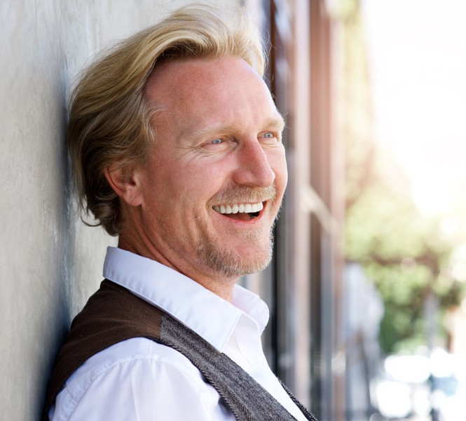 Man smiling as he leans against a wall