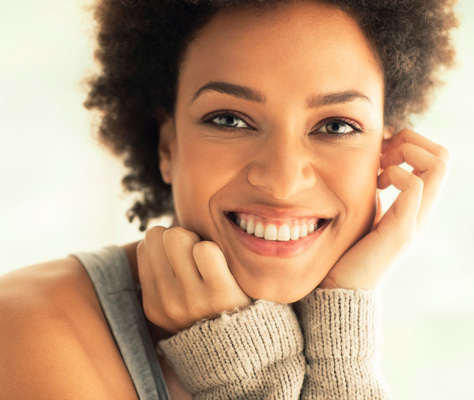 Woman smiling with her chin on her hands