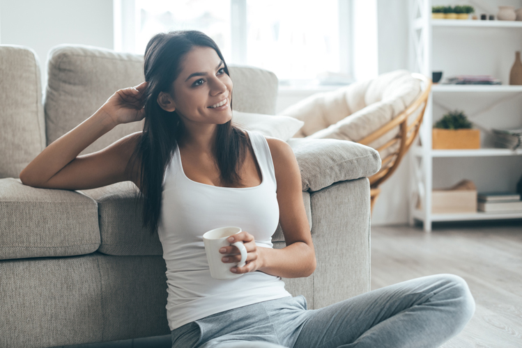 Woman sitting on the floor with a cup and smiling