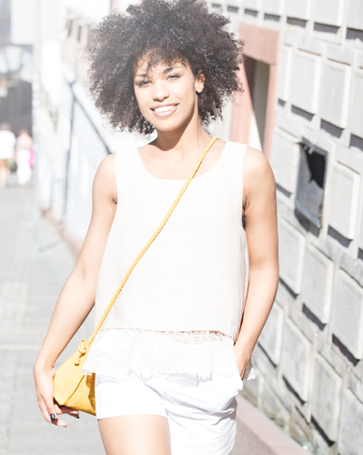 Woman smiling and walking with her hand in her pocket
