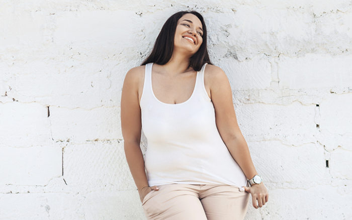 Woman with a big smile leaning against a wall