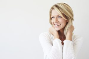 Woman holding her hair back as she shows a big smile