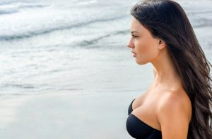 Woman looking out over the ocean with a bathing suit top on