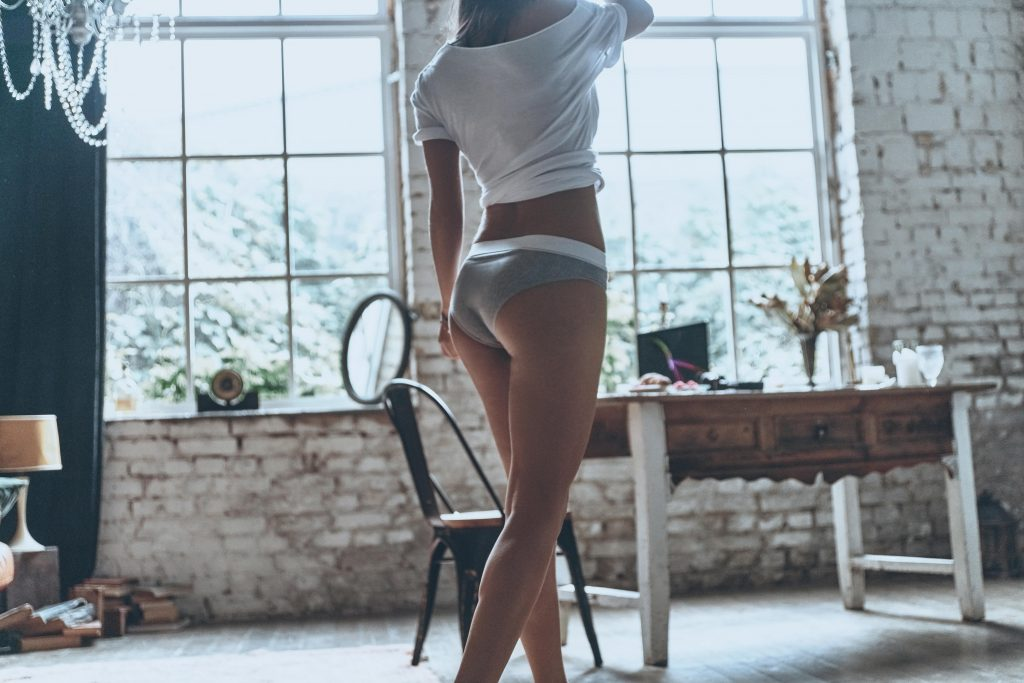 Woman walking across a room in her underwear and a shirt