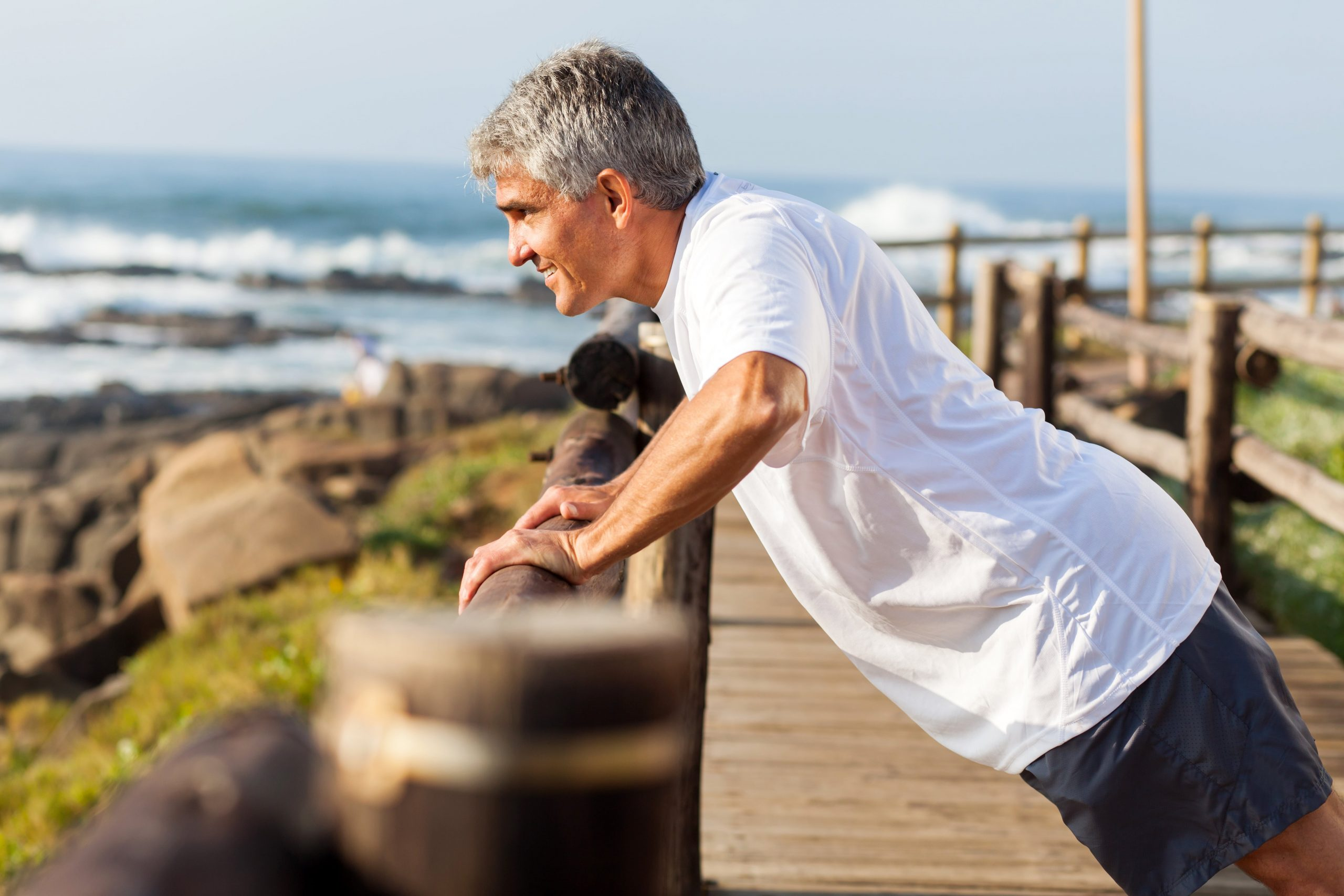 Older man stretching against a railing over the ocean